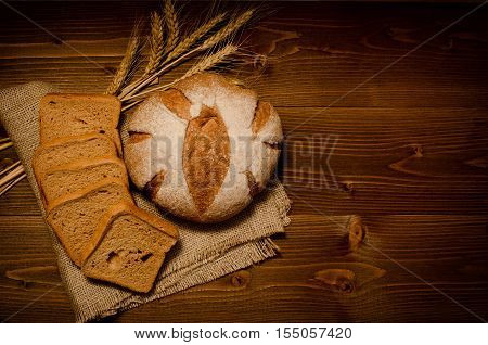 Top view of round rye bread on sackcloth square pieces of bread wheat ears on the wooden table space for text