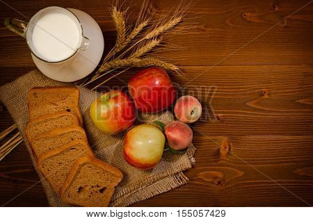Top view harvest on a wooden table: apples peaches rye bread a jug of milk ears on sackcloth free space for text