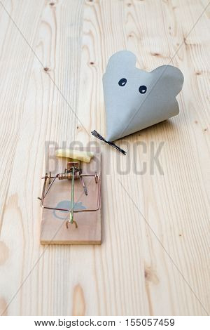 Mouse made of paper and mousetrap with cheese on wood. Good bait catches mice