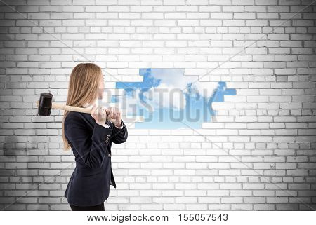 Woman has crashed a white brick wall with sledgehammer. Sky is seen through the hole. Concept of road to freedom
