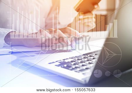 Close up of woman's hand working with laptop touchpad and holding small black notebook. Graphs are seen at the foreground. Concept of office work. Toned image. Double exposure