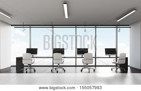 Front view of row on computers on long desk in office with panoramic windows. Concept of open office.