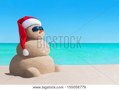 Happy sandy snowman in Christmas Santa Claus hat at sunny sea beach New Year holiday vacation concept for traveling to hot south countries