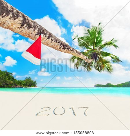 Red Santa hat on coconut palm tree at perfect tropical white sandy ocean beach at season year 2017 sand inscription. Holiday concept for New Years and Christmas Cards. Seychelles Mahe island.