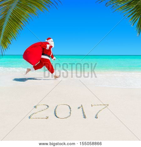 Christmas Santa Claus run at ocean tropical sandy palm beach with large sack full of gifts - season 2017 New Year vacation and travel agencies price discounts concept