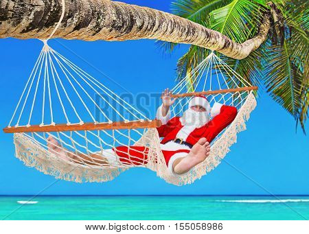 Santa Claus bathe in the sun in white cozy mesh hammock under palm tree shadow at tropical paradise ocean beach - New Year and Christmas Eve holidays travel agencies tour price reduction concept
