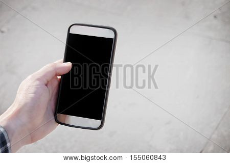 Hand holding smartphone over neutral floor background