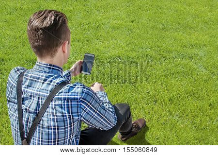 Young Man Using His Phone On Grass Field