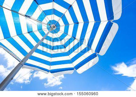 Blue striped beach umbrella on the beach.