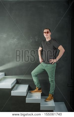 Studio Shooting Young Brutal Guy. Man In Sunglasses, T-shirt, Jeans And High Boots On A Background O