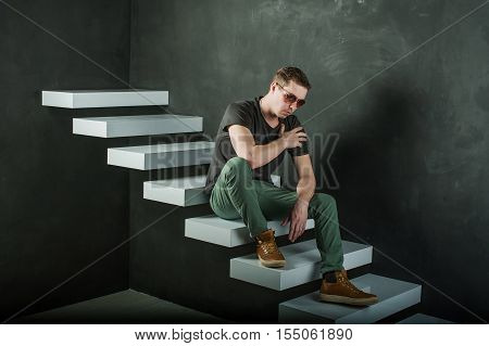 Studio Photography Young Brutal Guy. Man In Sunglasses, T-shirt, Jeans And High Boots On A Backgroun