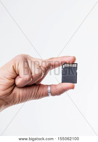Close up on single hand holding dark colored blank SD card over isolated white background