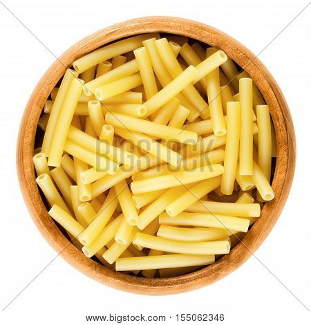 Macaroni pasta in wooden bowl, Italian maccheroni, short-cut noodles in the shape of narrow tubes. Uncooked dried durum wheat semolina pasta. Isolated macro food photo over white background.