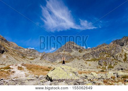 Yoga exercising in Tatry mountains - meditation in lotus pose namaste. Tourist trekking in Beautiful Mlynicka dolina on the way to Bystre sedlo - in slovakian high Tatra mountains. Summer panorama with great weather and blue sky