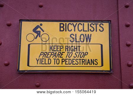 A yellow bicyclists slow sign on a red background