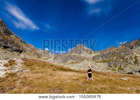 Yoga exercising in Tatry mountains Headstand Shirshasana. Tourist trekking in Beautiful Mlynicka dolina on the way to Bystre sedlo - in slovakian high Tatra mountains. Summer panorama with great weather and blue sky