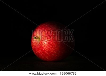 Big red apple in drops of water close-up on a dark background