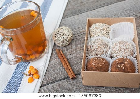 raw vegan energy balls with sea buckthorn tea with honey in a transparent Cup. sugar free candies  and warming herbal tea with berries