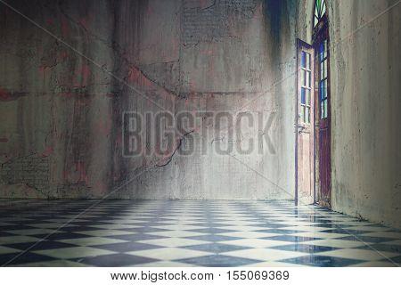 Grey concrete wall with tile floor with classic door open