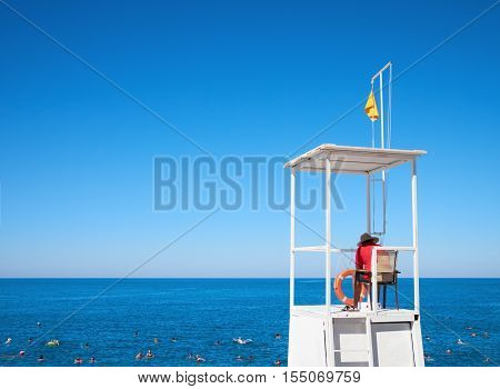 Lifeguard on tower to watching people floating in sea