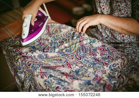 Adult Woman Irons Colorful Patterned Cloth Electric Iron On An Ironing Board. Close Up