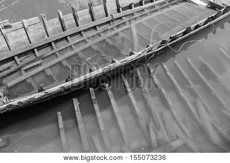 discarded wood boat in canal - Back and white Color