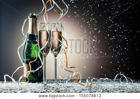 Bottle of champagne and wine glasses with ribbons