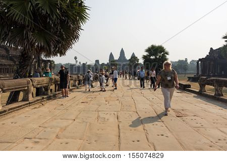 ANGKOR WAT CAMBODIA - JANUARY 27 2015: Tourists walking to the entrace of Angkor Wat temple in Cambodia. Angkor Wat is the largest Hindu temple complex and religious monument in the world