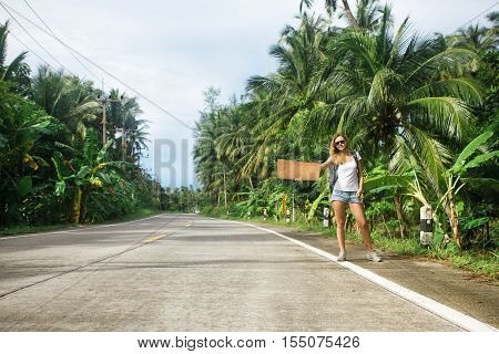 young woman hitchhiking along a road. stock image.