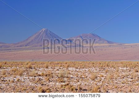 Highly symmetric conic shaped volcano with smaller neighbor and some grass in its base.