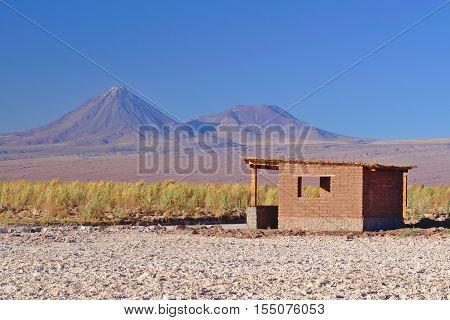 Small adobe house in the desert on salt terrain and near two volcanoes.