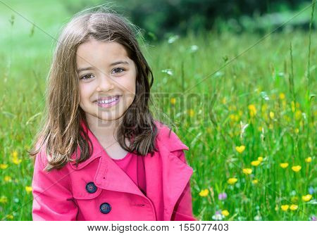 Happy Cute Child Sitting In A Grass Of A Flower Garden