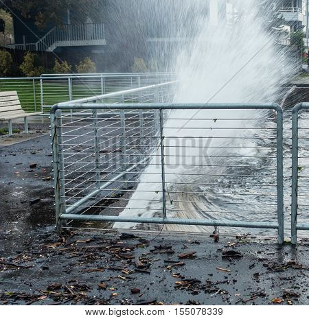 A wave of water blast against a sea wall at Des Moines Marina in Washington State.