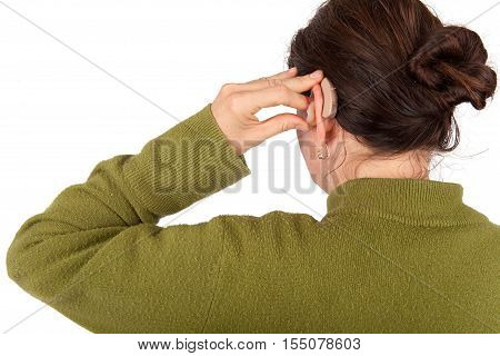 Woman inserting her hearing aid. Isolated on white background.