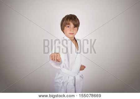 Karate kid wearing white kimono posing isolated on gray background with vignette