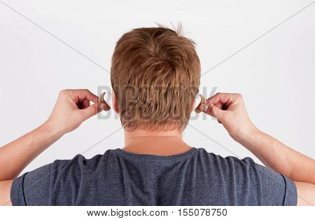 Back view of a deaf man's head and hands inserting his hearing aids.