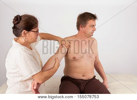 Middle aged man receives bowen massage treatment for his arm. Bowen is a holistic system of healing.