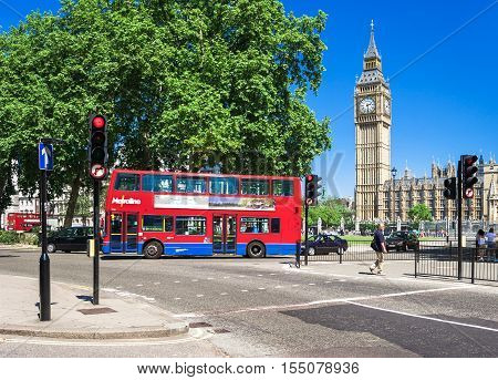 London UK - June 10 2006: Red Double-decker bus in front of symbol of London Big Ben tower. The Palace of Westminster commonly known as the Houses of Parliament.