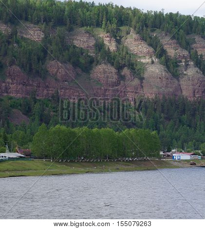 Wooded steep mountains near the river .