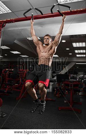 Muscular shirtless man doing pulling up on horizontal bar.