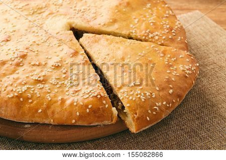 Tasty pie with minced meat on wooden table.