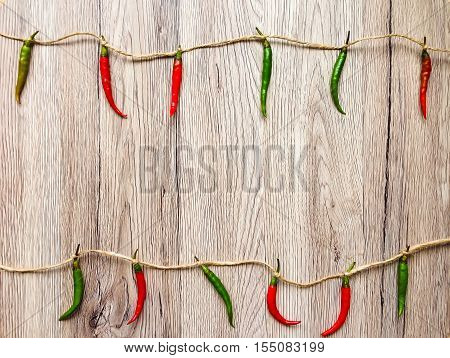 Bright Background With Peppers Hanging On Twine. Flat Lay, View From Above, Wooden Background
