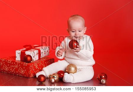 Cute baby boy 1 year old playing with christmas decorations, presents over red. Little child wearing trendy knitted clothes in room.
