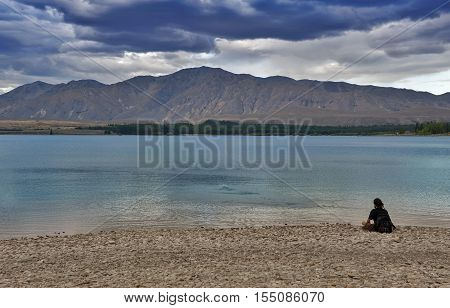 Tekapo, New Zealand - February 2016: Unidentified Man Sitting And Looking At Lake Tekapo, South Isla