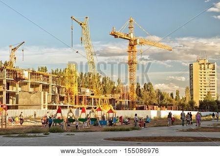 VOLGOGRAD - SEPTEMBER 9: The construction of a new monolithic apartment house near a Playground where children play . September 9 2016 in Volgograd Russia.