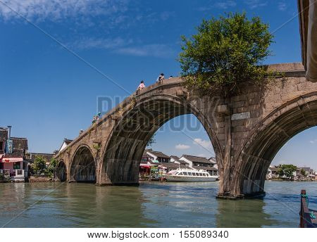 ZHUJIAJIAO CHINA - AUGUST 30 2016: Tourists see the sights of ancient water town with a history of more than 1700 years from Fangsheng bridge over canal in Zhujiajiao China on August 30 2016.