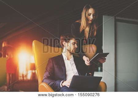 Businesswoman in red dress and jacket showing information on screen of her tablet to her boss on yellow armchair in formal suit with white laptop, luxury office