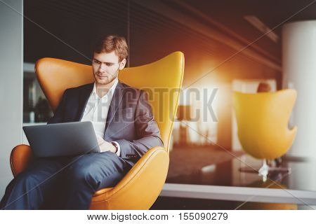 Young serious successful man entrepreneur in formal business suite with a beard sitting on yellow armchair working on laptop in luxury office interior, preparing to business meeting