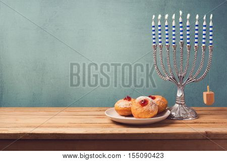 Hanukkah background with menorah and sufganiyot on wooden table