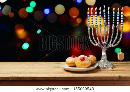 Hanukkah holiday sufganiyot with menorah on wooden table over night bokeh background